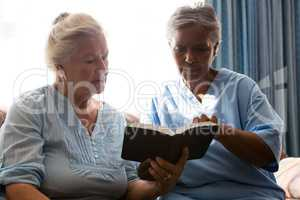 Doctor with senior woman reading book while sitting in retirement home