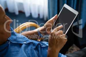 View of senior man using digital tablet at nursing home