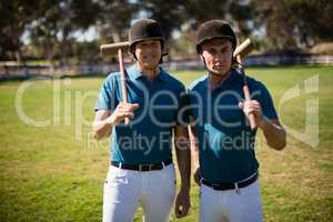 Two male jockeys standing in the ranch