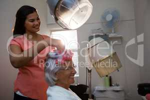 Smiling beautician removing curlers from senior woman hair