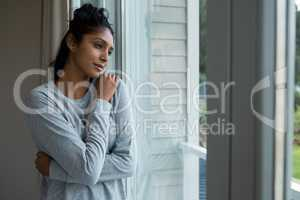 Thoughtful woman with hand on shoulder by window