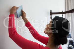 Woman holding color swatch by wall