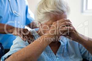 Nurse consoling senior woman at nursing home