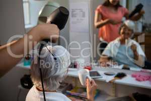 Beautician drying senior woman hair reflecting on mirror