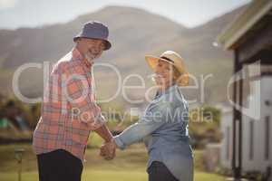 Senior couple holding hands and standing in lawn on a sunny day