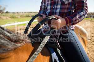 Mid section of girl riding a horse in the ranch
