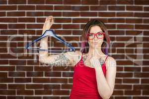Confused woman holding hanger against brick wall