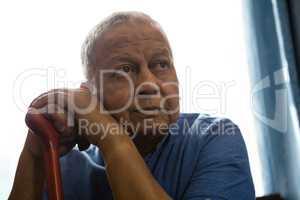 Thoughtful senior man holding walking cane while sitting at nursing home