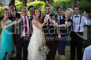 Newly married couple and guests holding glasses of champagne