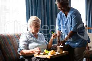 Doctor standing by senior woman eating food at table