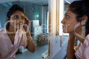 Woman reflecting on mirror in bathroom