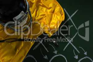 American football jersey, referee whistle and head gear lying on green board with strategy drawn on