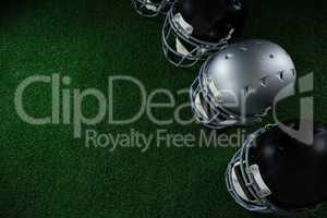American football head gears arranged over artificial turf
