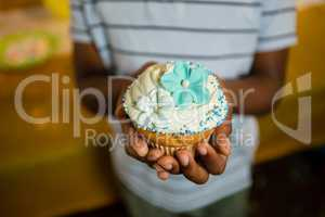 Mid section of boy holding decorated cupcake during birthday
