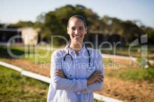 Smiling female vet with arms crossed standing at barn