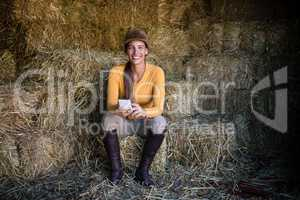 Happy female jockey using phone while sitting on hay in stable
