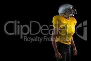 American football player standing against a black background