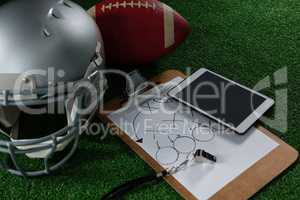 American football head gear, tablet, whistle and football on artificial turf