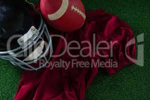 American football jersey, head gear and football lying on artificial turf