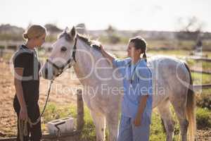 Jockey talking to vet while standing by horse at barn