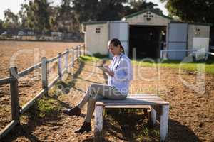 Female vet using digital tablet while sitting at barn