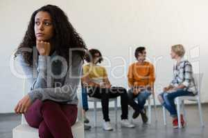 Thoughtful woman sitting on chair with friends in background