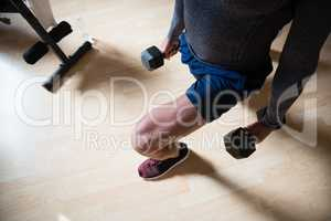 Low section of male athlete exercising lunges in fitness club