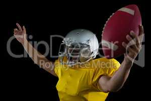 American football player cheering with ball in his hand
