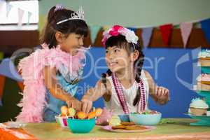 Cute girl having confectionery during birthday party