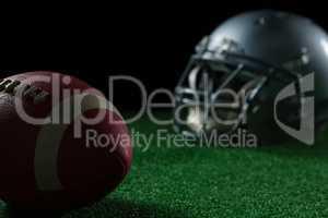 American football head gear and football on artificial turf