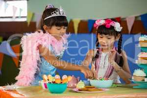 Cute girls having confectionery during birthday party