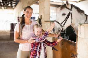 Portrait of sisters stroking horse