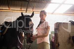 Side view of female jockey stroking horse