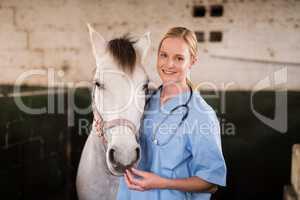 Portrait of smiling female vet standing by horse