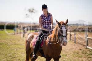 Portrait of smiling jockey horseback riding