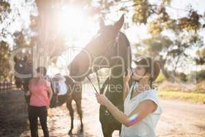 Female friends stroking horses at barn