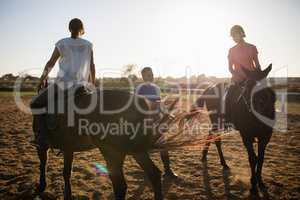 Trainer guiding female friends in riding horse