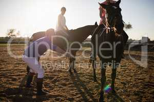 Trainer training friends in riding horse at barn
