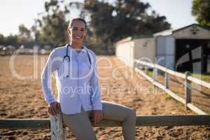 Smiling female vet sitting on wooden fence at barn