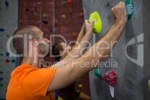 Male trainer guiding athlete in climbing wall at health club