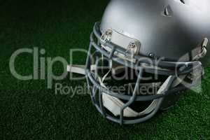 American football head gear over artificial turf