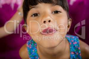 Girl making funny faces during birthday party at home