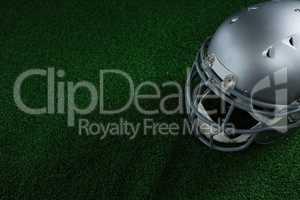 American football head gear lying on artificial turf