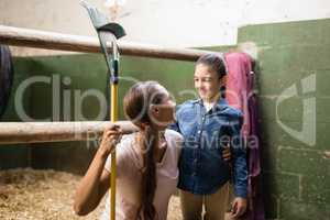 Smiling female jockey holding rake while talking to sister