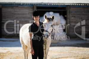 Confident female jockey standing by white horse at barn