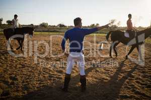 Male trainer guiding young women in riding horse