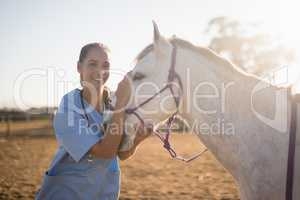 Smiling female vet stroking horse at barn