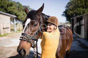 Portrait of smiling female jockey stroking horse