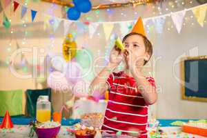Cute boy blowing party horn during birthday party