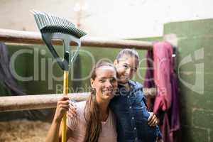 Portrait of female jockey holding rake with sister